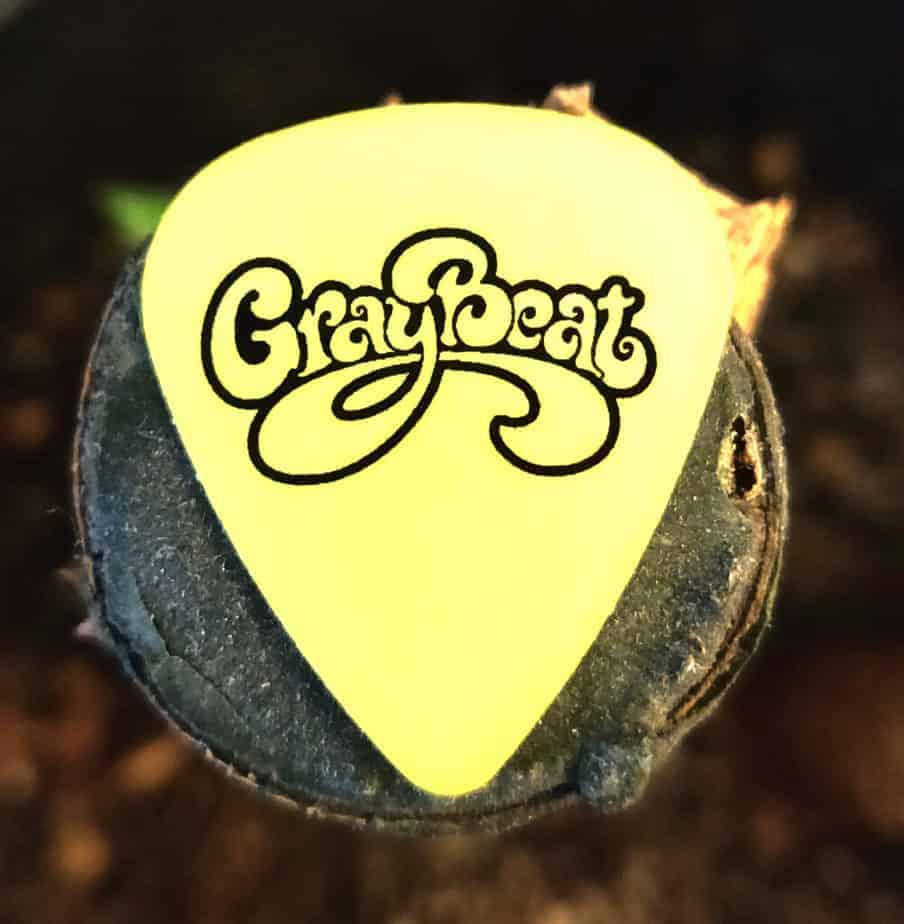Luminescent yellow guitar pick with GrayBeat emblem imprinted